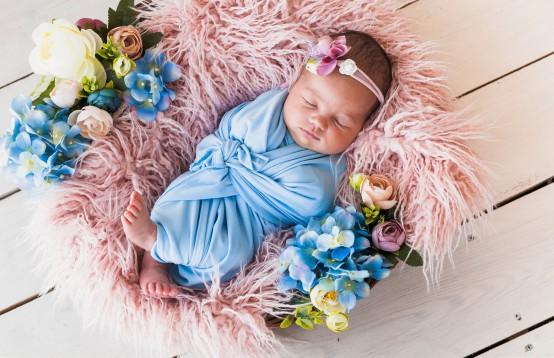 Slapende baby omringt met bloemen